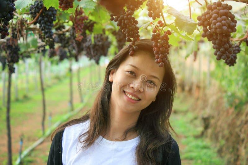 Asiatiskt kvinnaleende och grupp av druvor i vingård Vinodling vin royaltyfria bilder