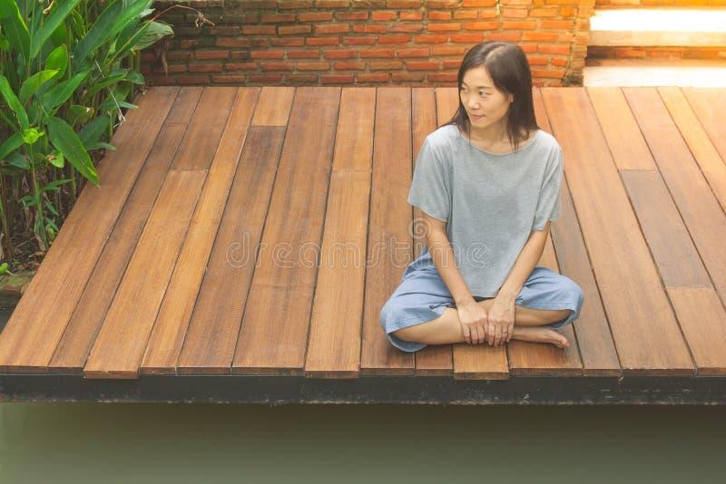 Asiatiskt kvinnasammanträde kopplar av på den träterrass eller farstubron nära dammet i trädgården royaltyfria bilder