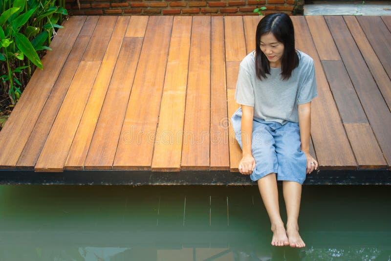 Asiatiskt kvinnasammanträde kopplar av på den träterrass eller farstubron nära dammet i trädgården royaltyfri bild