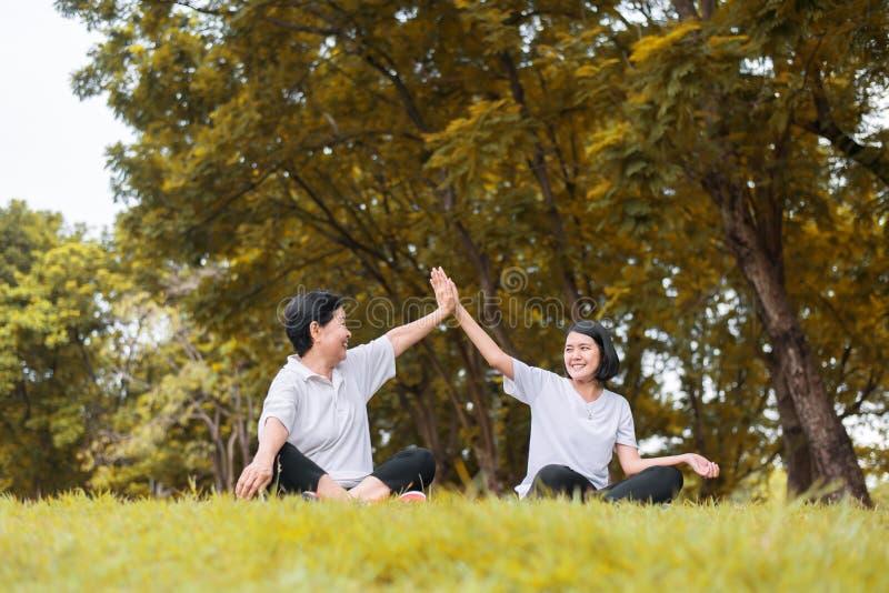 Asiatiskt kvinnasammanträde och kopplar av på parkerar sund och livsstilbegreppet i morgonen tillsammans, lyckligt och att le, de arkivfoton