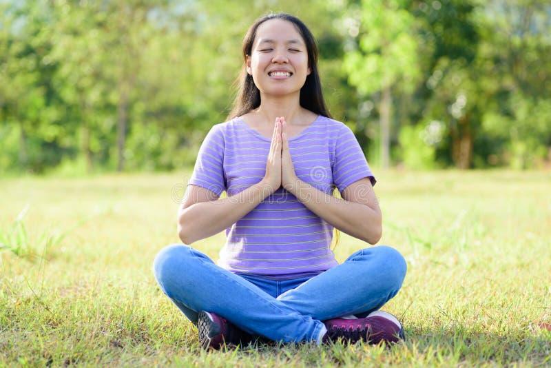 Asiatiskt kvinnasammanträde och meditation i utomhus- arkivfoto