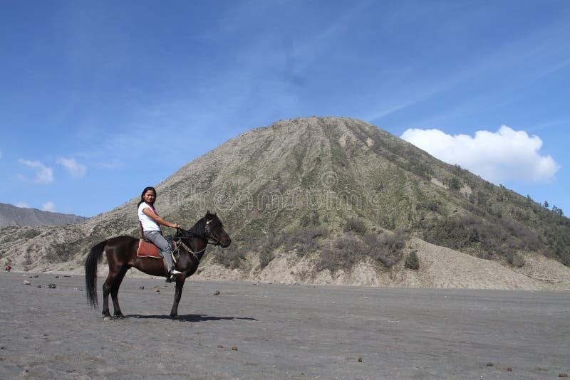 Asiatiskt kvinnasammanträde på en häst med bergbakgrund arkivbilder