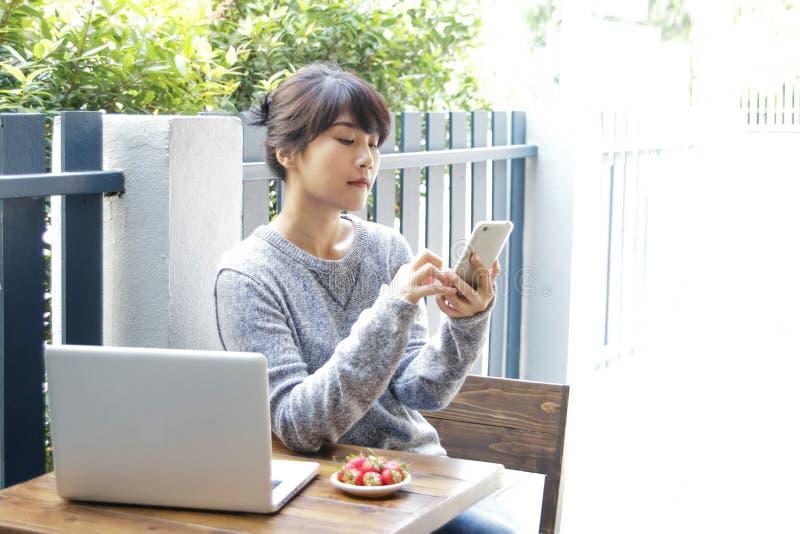 Asiatiskt kvinnasammanträde på en tabell och en användasmartphone hemma Typ royaltyfri fotografi