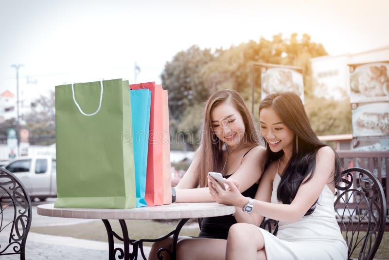 Asiatiskt kvinnasammanträde på lagerkafét och den hållande ögonen på smartphonen på shoen royaltyfri bild