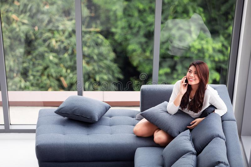 Asiatiskt kvinnasammanträde på soffan nära stora glass fönster som kopplar av alo arkivfoto