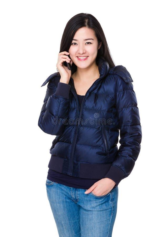 Asiatiskt kvinnasamtal till mobiltelefonen arkivbild