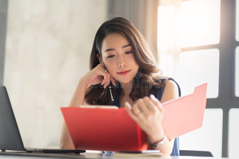 Asiatiskt kvinnligt arbete i kontoret arkivfoto