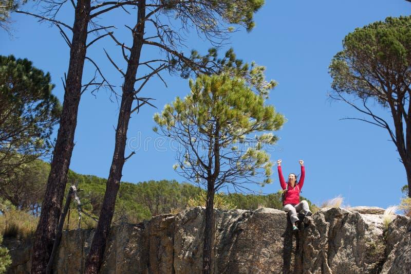 Asiatiskt kvinnligt fotvandraresammanträde på kanten av berget med lyftta händer royaltyfria foton