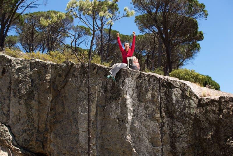 Asiatiskt kvinnligt fotvandraresammanträde på kanten av berget med lyftta händer arkivfoto