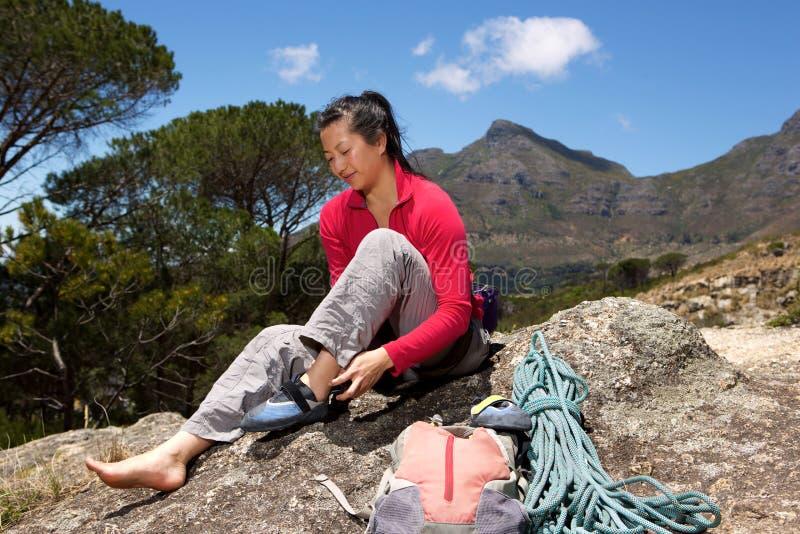 Asiatiskt kvinnligt fotvandraresammanträde på maximumet och att förbereda sig för vaggar klättring arkivfoto