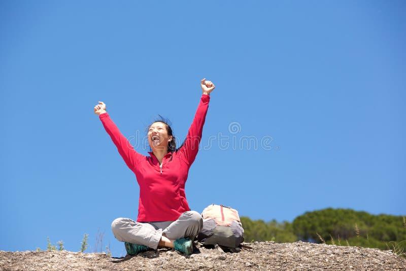 Asiatiskt kvinnligt fotvandraresammanträde utomhus med lyftta händer royaltyfri foto