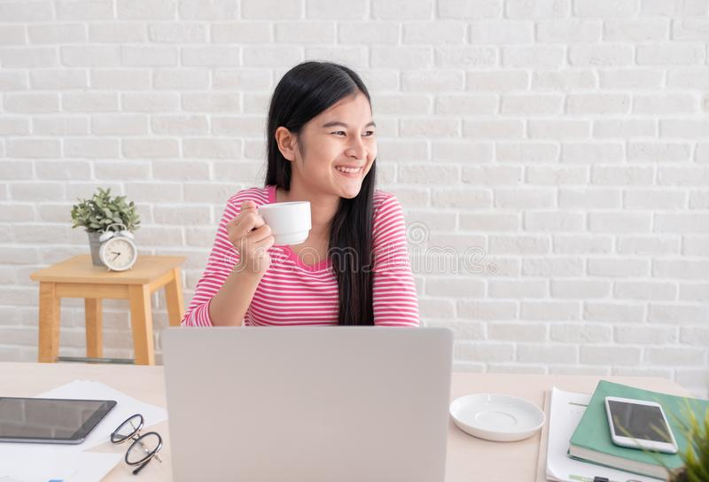 Asiatiskt kvinnligt freelancerleende- och drinkkaffe med kopplar av emotio arkivbild