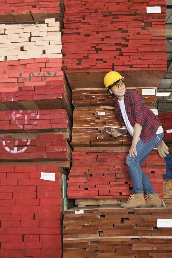 Asiatiskt kvinnligt industriarbetareanseende på staplade träplankor som rymmer minnestavlaPC royaltyfria bilder