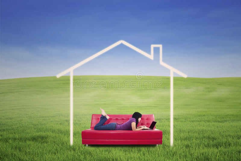 Asiatiskt kvinnligt ligga på soffan i det utomhus- dröm- huset arkivfoto