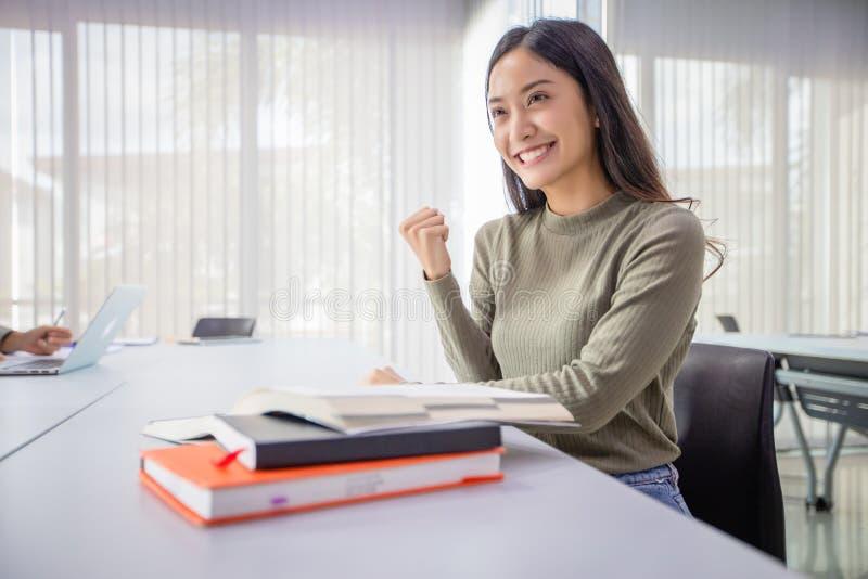 Asiatiskt leende för kvinnastudenter och spännande med lyftta armar hon läseboken och granskar också boken för examen royaltyfri foto