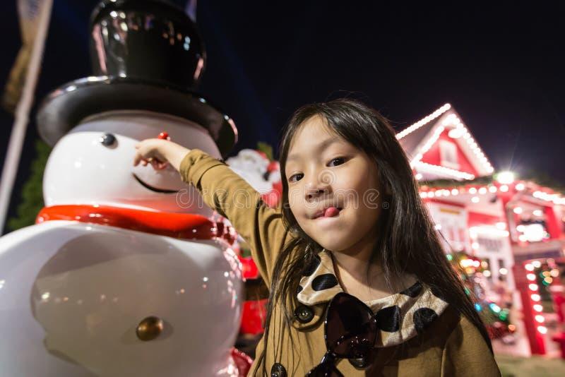 Asiatiskt liten flicka- och snögubbeanseende i fältet, nattsikt i bakgrunden av huset och julträd i nya year's royaltyfri fotografi