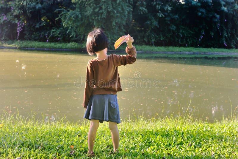 Asiatiskt liten flickakast ett blad till sjön, medan beundrar det nat arkivbilder