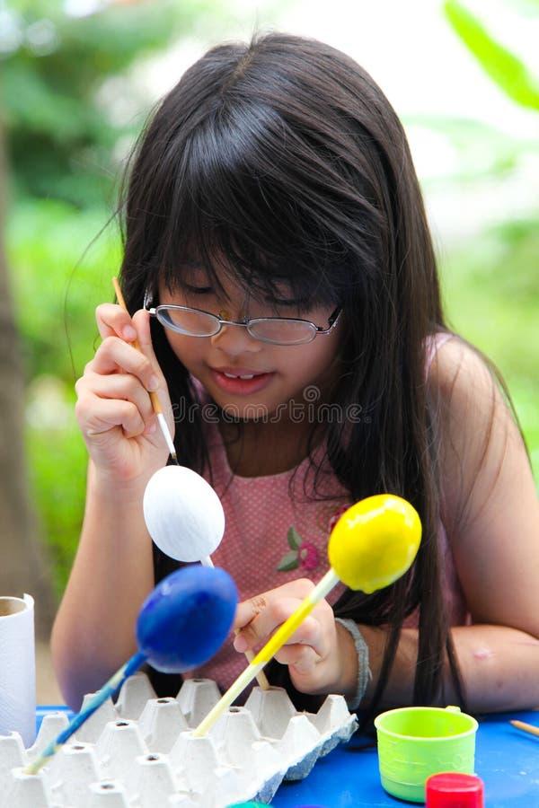 Asiatiskt liten flickamålningägg arkivbild