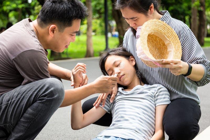 Asiatiskt litet barn med värmeslaglängden, hög temperatur, svindel, svindel, sjuk dotter på en solig dag, gullig flicka som har e royaltyfri bild