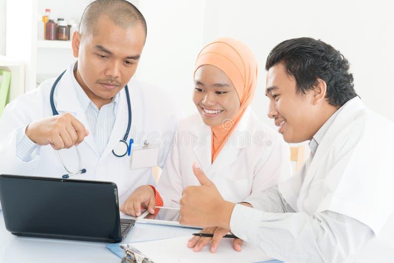Asiatiskt möte för medicinskt lag på sjukhuskontoret och tummar upp royaltyfri bild