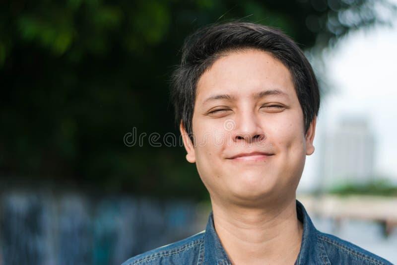 Asiatiskt mananseende och visning hans lyckliga le arkivbild