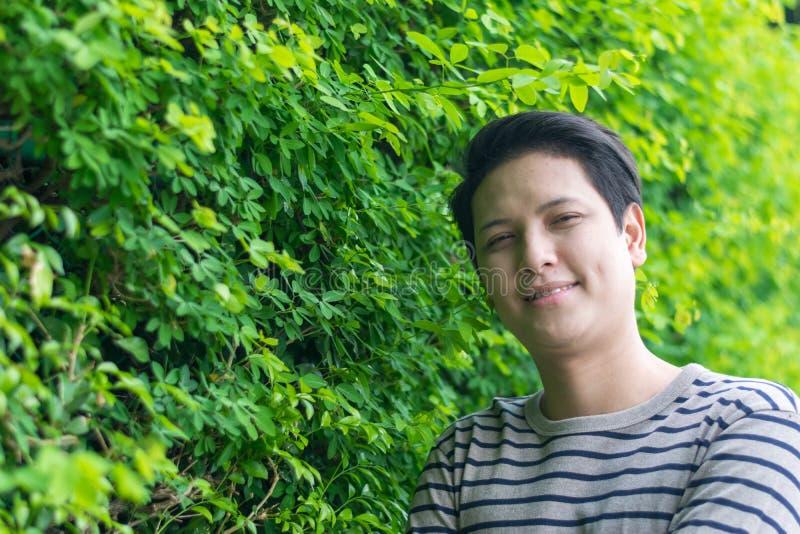 Asiatiskt mananseende och visning hans lyckliga le royaltyfri foto