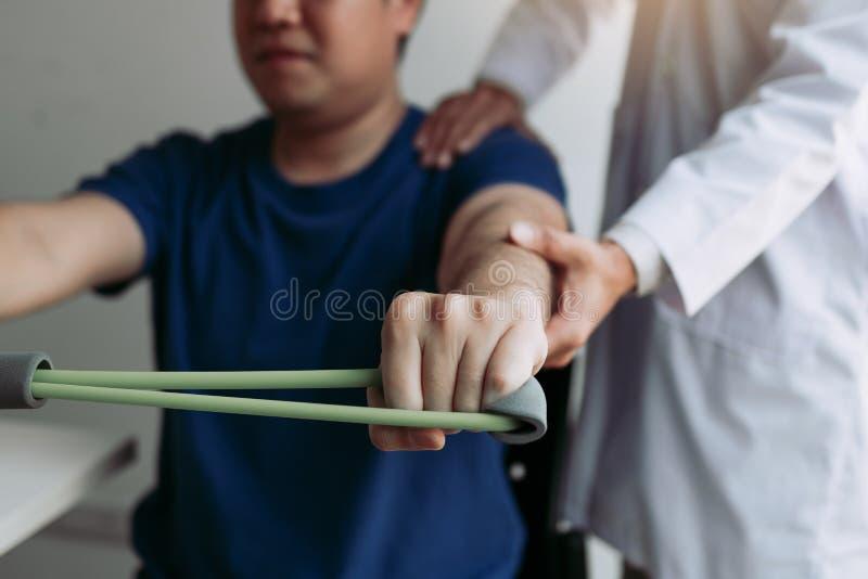 Asiatiskt manligt nedstigningsarbete för fysisk terapeut med patienten som gör sträcka övning med en böjlig övningsmusikband i kl royaltyfria bilder