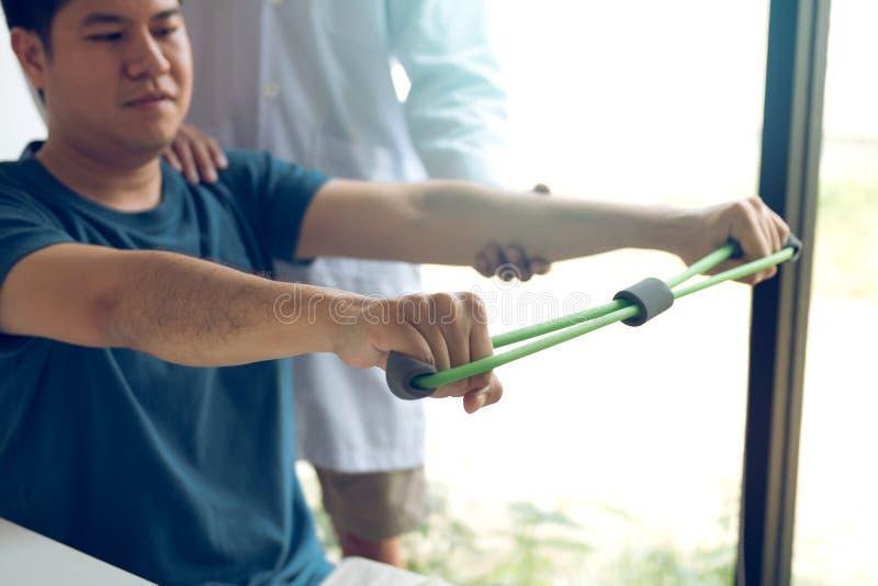 Asiatiskt manligt nedstigningsarbete för fysisk terapeut med patienten som gör sträcka övning med en böjlig övningsmusikband i kl royaltyfri foto
