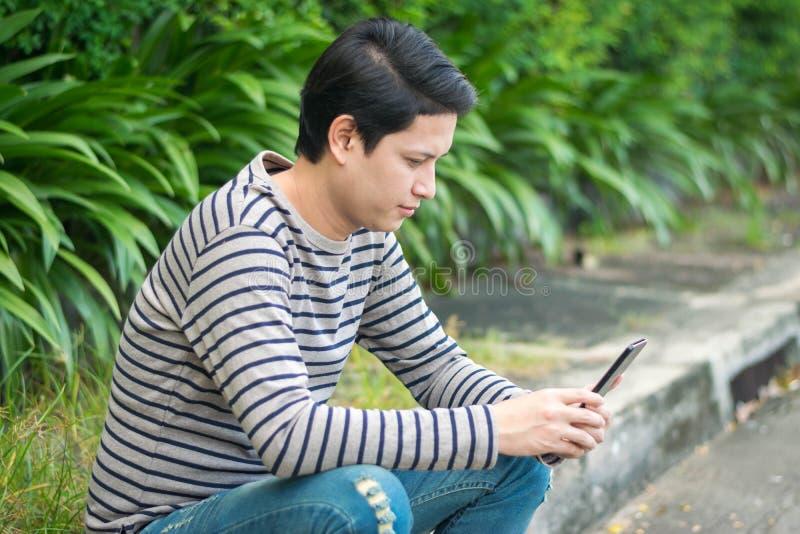 Asiatiskt mansammanträde och användasmartphone arkivfoto