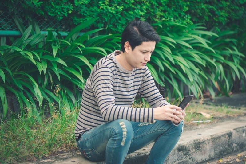 Asiatiskt mansammanträde och användasmartphone royaltyfria bilder
