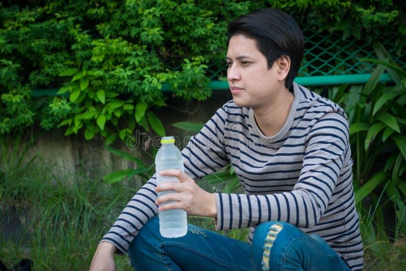 Asiatiskt mansammanträde och dricksvatten royaltyfria foton