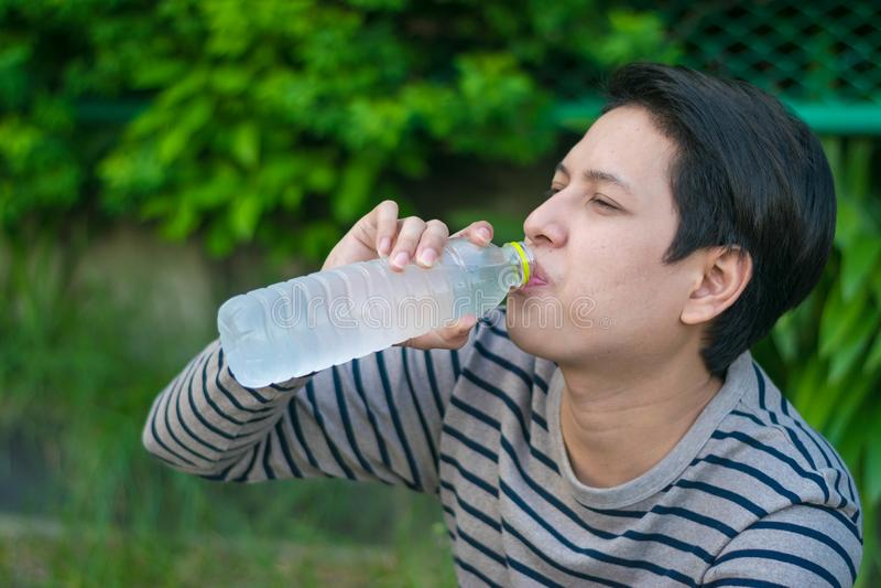 Asiatiskt mansammanträde och dricksvatten royaltyfria bilder
