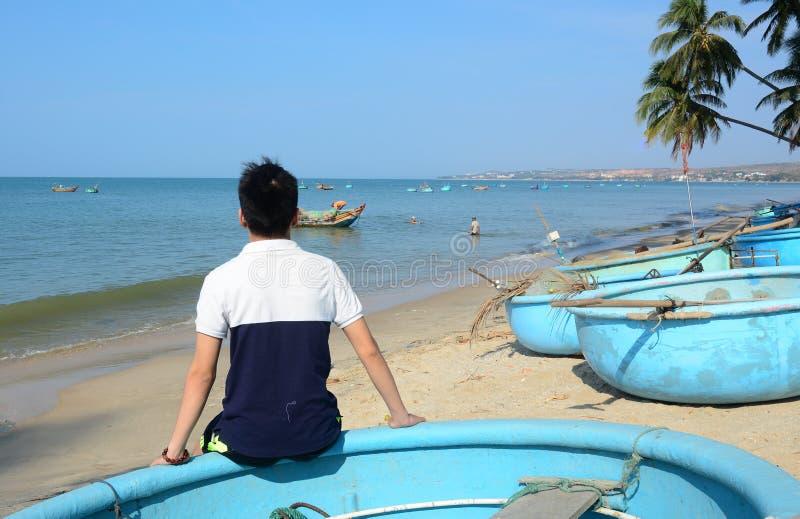 Asiatiskt mansammanträde på stranden royaltyfri foto