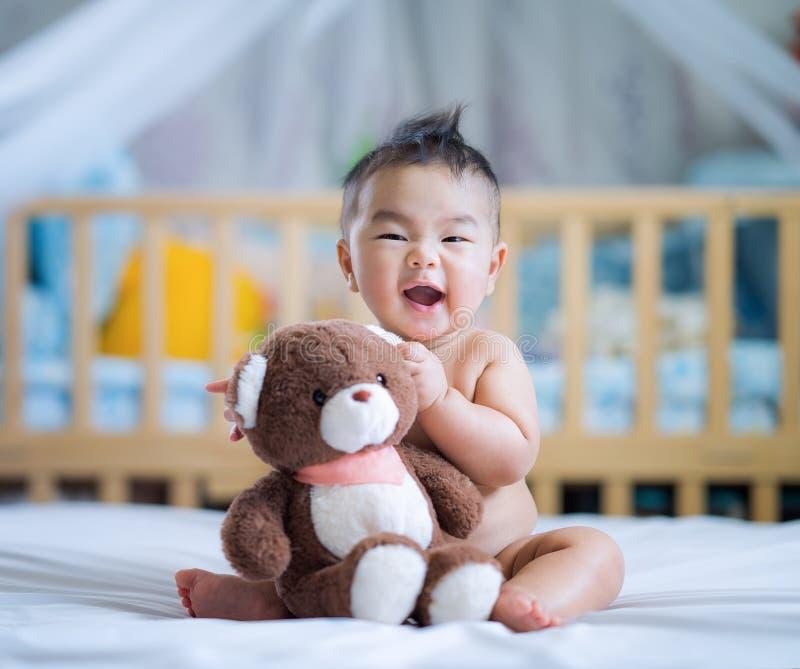 Asiatiskt nyfött behandla som ett barn sitter och kramar en nallebjörn arkivfoto
