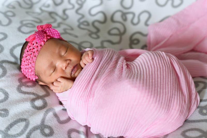 Asiatiskt nyfött behandla som ett barn sleepin i bärande huvudbindel för rosa torkduk royaltyfria foton