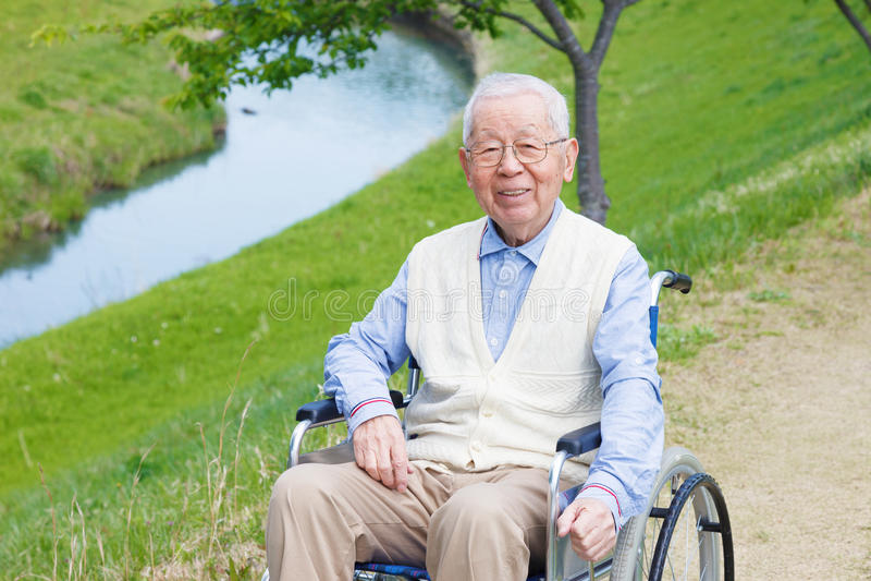 Asiatiskt sammanträde för hög man på en rullstol arkivfoton