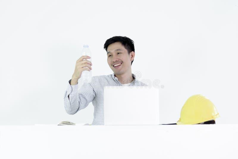 Asiatiskt sammanträde för man för anställdteknikerlön på skrivbordet och att dricka arkivfoton