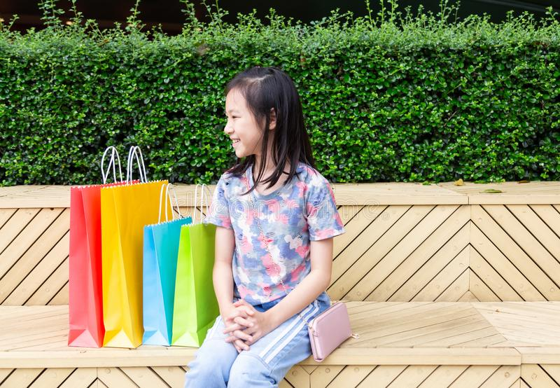 Asiatiskt sitta för flicka som är utomhus- med shoppingpåsar arkivfoton