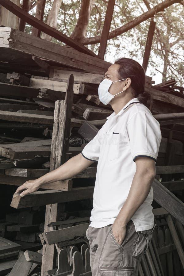 Asiatiskt skydd för maskering för framsida för mankläder medicinskt i den wood fabriken fotografering för bildbyråer