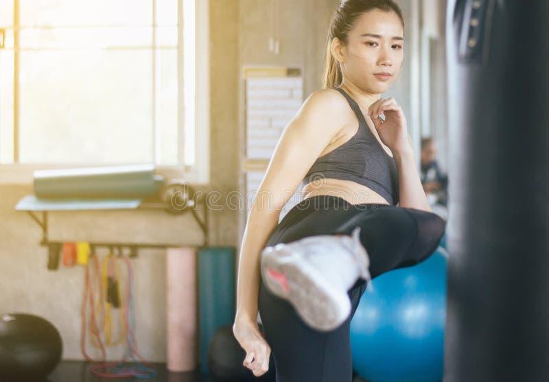 Asiatiskt stansa för kvinnaboxare och spark på en boxas idrottshall, kvinnlig boxareutbildning på stansa påse arkivbild