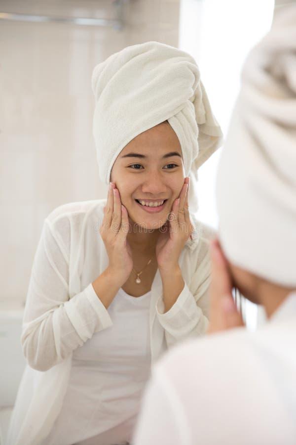 Asiatiskt ta för ung kvinna att bry sig hennes framsida med båda händer, leende royaltyfri bild
