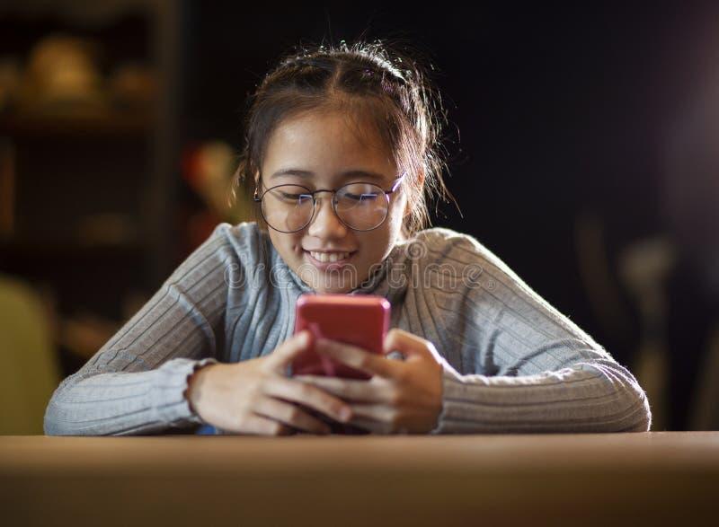 Asiatiskt tonåringläsningmeddelande på den smarta telefonskärmen med lycka som ler framsidan royaltyfri bild