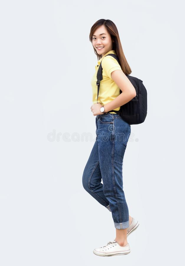 Asiatiskt tonårs- hållryggsäckbälte och att gå handling på vit royaltyfri fotografi
