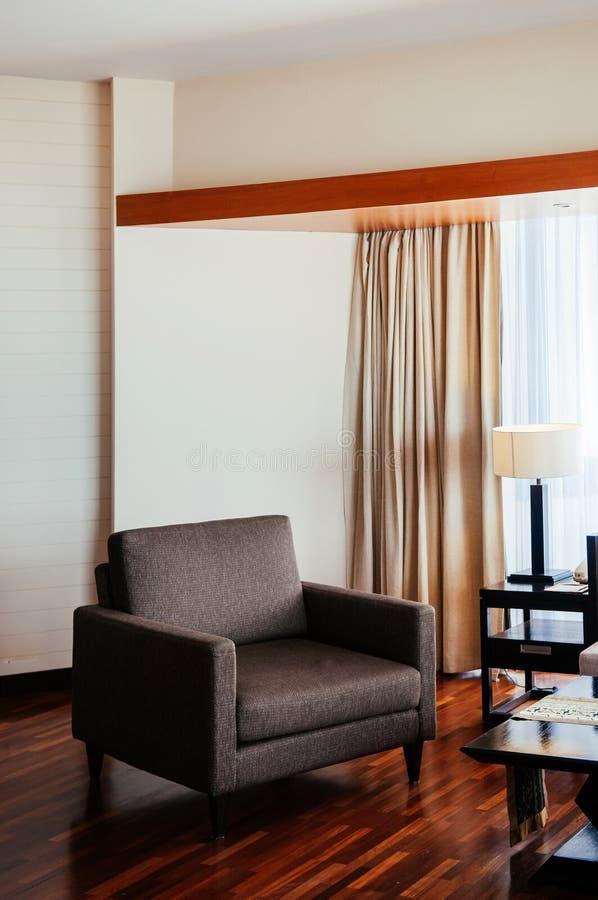 Asiatiskt tropiskt golv för stilhotellrumträ med den moderna tygfåtöljen arkivbild