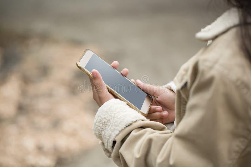 Asiatiskt ung flickabarn som spelar den smarta telefonen för mobil i vinterdräkt arkivbild