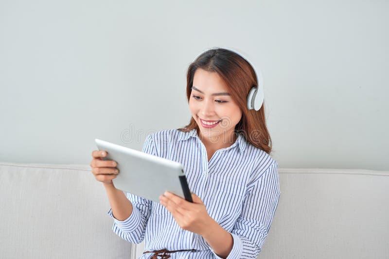 Asiatiskt ungt n?tt kvinnaarbete p? minnestavlan att lyssna musikh?rlurar royaltyfria bilder