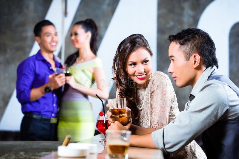 Asiatpar som flörtar och dricker på nattklubbstången royaltyfria bilder