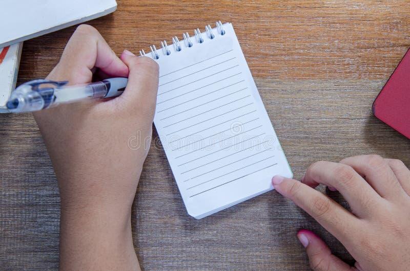 Asiats kvinnahänder som ner skriver på den bästa sikten för bok på trätabellen arkivfoto