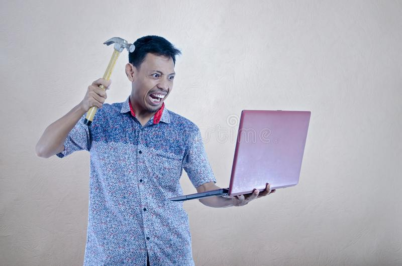 Asiats unga män som försöker att bryta en bärbar dator vid hummeren royaltyfria foton