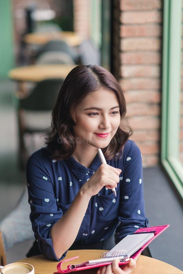 Asiatyong kvinna i kafét nära fönstret, tänka och writien arkivfoto
